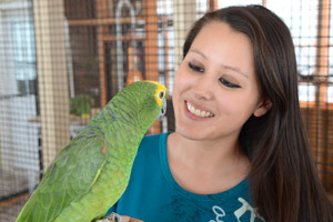 Parrot intern Kaila Huhtasaari of Pelkie, Michigan, holding a parrot