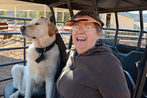 Sandy Batalden riding in a golf cart with a dog at Best Friends Animal Sanctuary