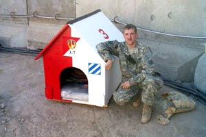 US soldier Peter kneeling next to a dog house