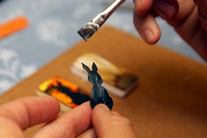 Woman creating and painting an upcycle rabbit necklace
