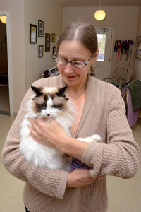 Caregiver holding Montana the special-needs cat