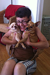 Woman snuggling two small tan dogs
