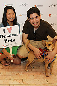 "Couple with their adopted dog. Woman is holding a sign that says ""I Love Rescue Pets."""