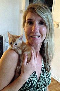 Foster mom holding an orange tabby kitten