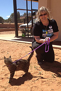 Holly Gingles walking a cat at Best Friends Animal Sanctuary