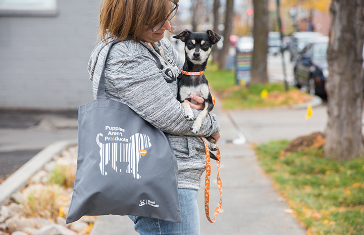 Woman holding a dog and a puppy mill advocacy tote