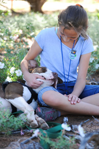 Preteen Danica petting Phinny the dog while volunteering at Best Friends Animal Sanctuary