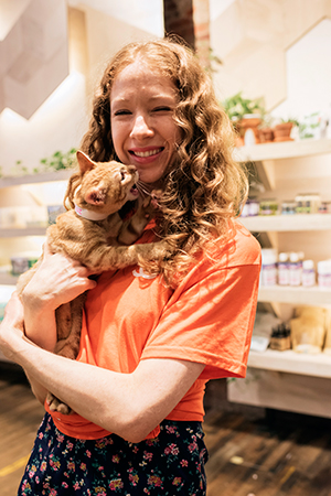 Woman holding a cat at the Urban Outfitters adoption event
