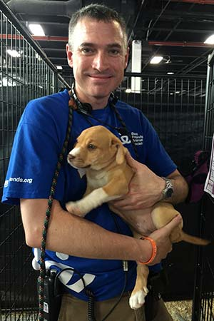 Volunteer Dale Musselman holding a puppy at an adoption event