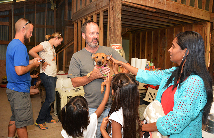 Here, Best Friends staff member Matt Fisher introduces puppy, Paige, to her new foster family