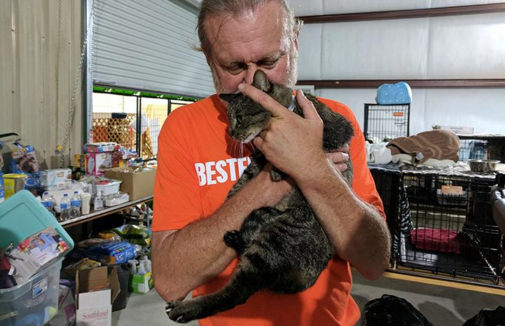 Best Friends staff member Mike Bzdewka snuggles a cat at the Rescue and Reunite Center