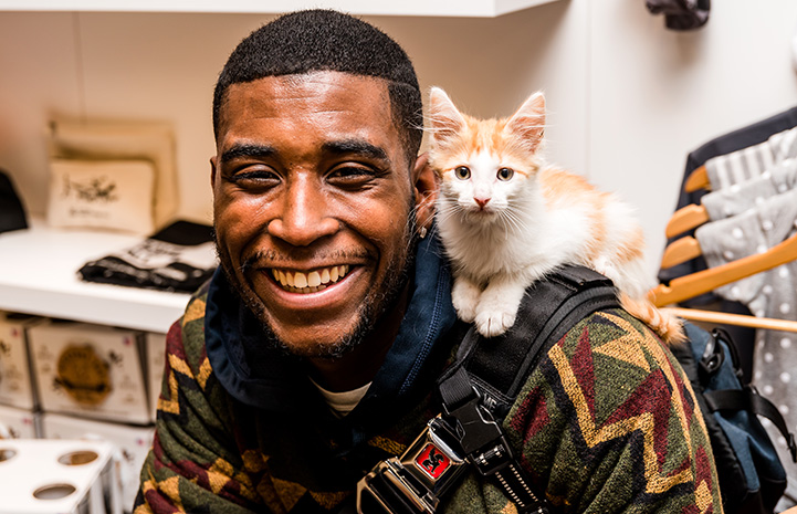 Smiling man with a white and cream colored kitten on his shoulder