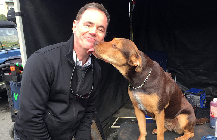 Bruce on the set of A Dog's Way Home getting a kiss from Shelby the dog