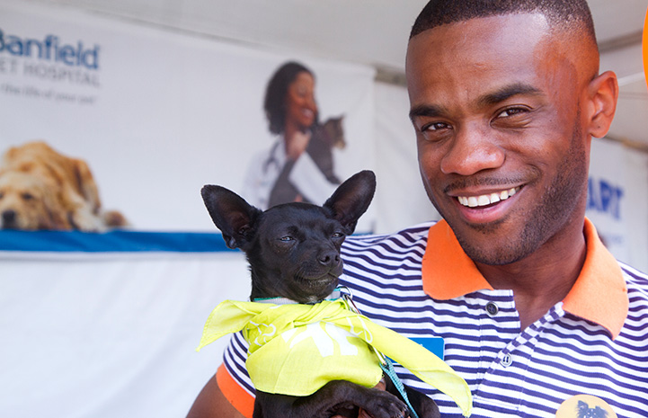 Smiling man holding the small black Chihuahua mix dog who he adopted