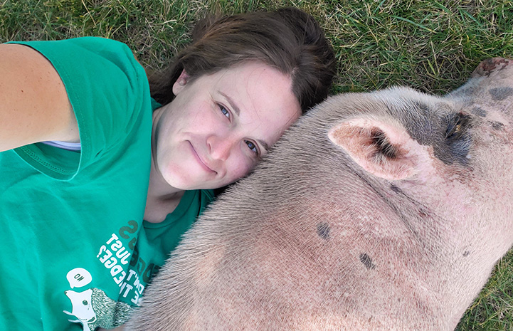 Jennifer West lying next to Diesel the pig