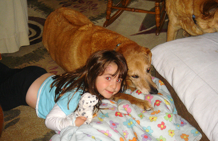 Young girl Hannah lying next to Arby the senior dog