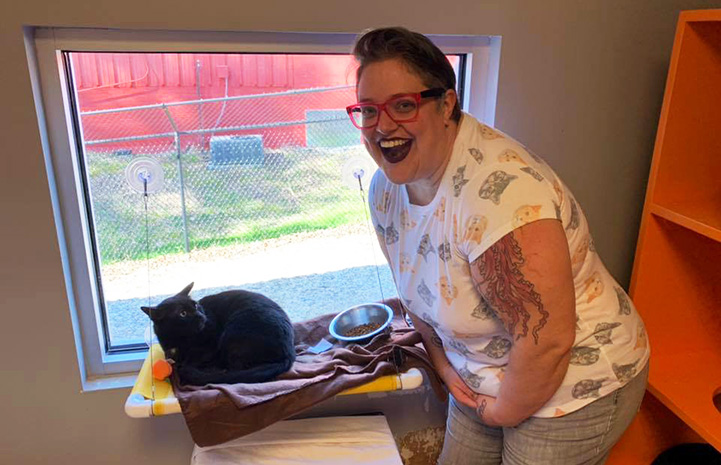 Woman with wide smile with the cat she's adopting in a window