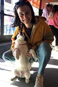 Smiling woman squatting on the ground and holding a black and white puppy up