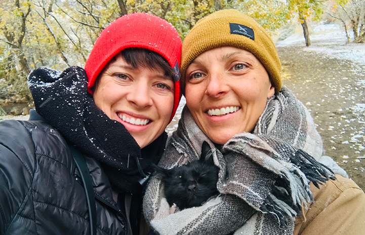 Two smiling women wearing hats and coats covered in a dusting of snow with Rafa the cat snuggled up in a scarf between them
