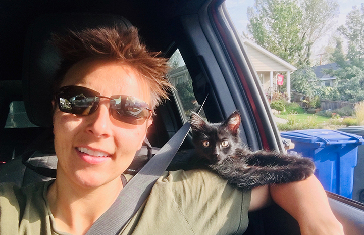 Woman in a car with Rafa the kitten on her shoulder