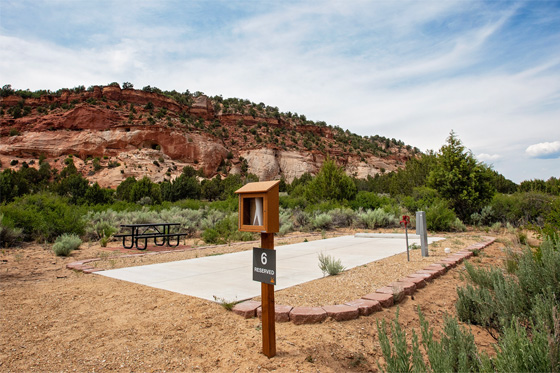 Open Angel Canyon RV site with a pad and sign in the front and red rock cliff in the back