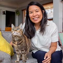 Angela Li sitting on a couch with a cat