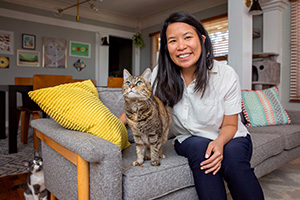 Angela Li sitting on a couch with two cats