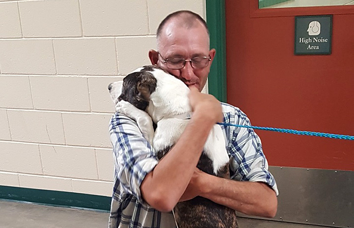 Man being reunited with his missing dog and giving him a hug