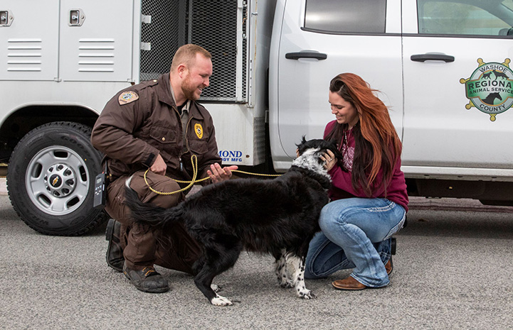 A male animal control officer kneeling down with a dog that a woman is hugging