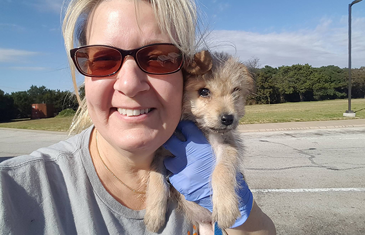 Sherri Bock Slattery volunteering to transport puppies and holding a puppy during a rest stop