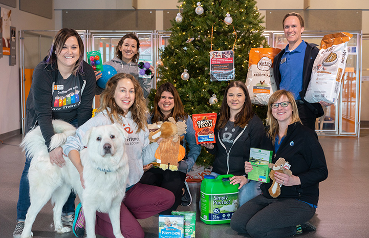 People from the Best Friends Pet Adoption Center in Salt Lake City posing with donations and a dog in front of a Christmas tree