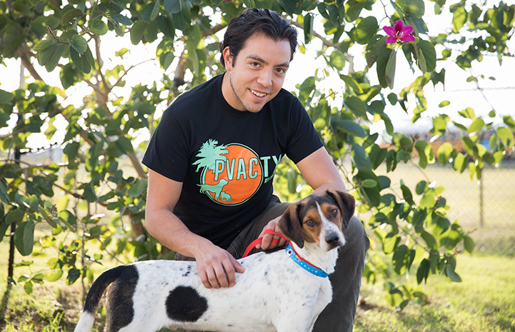 Luis Quintanilla kneeling down and petting a brown and white dog while wearing a PVAC TX T-shirt