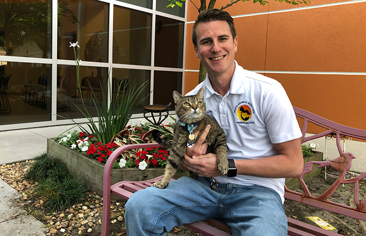 Spencer Conover at Pasco County Animal Services, sitting on a bench holding a brown tabby cat