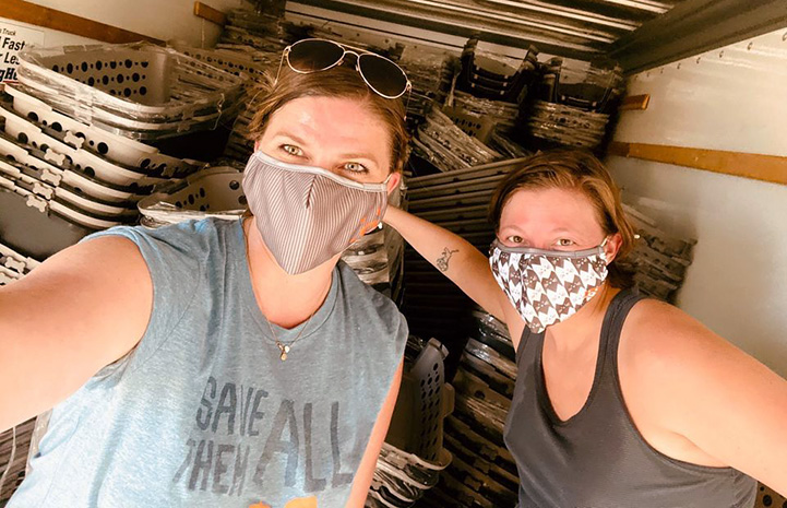 Two masked women standing in front of a huge pile of anima crates