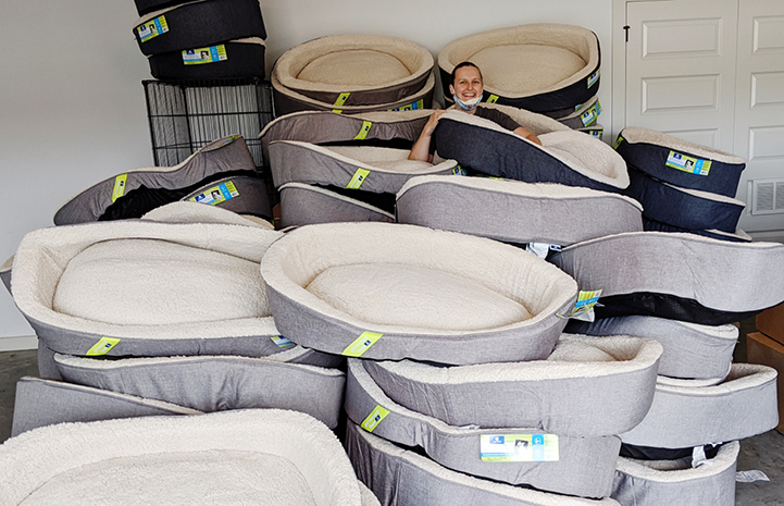 Woman standing in the middle of a huge pile of dog beds donated from Petco