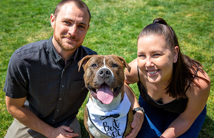 """Smiling couple with a smiling dog wearing a bandanna that says """"Best Dog"""" between them"""