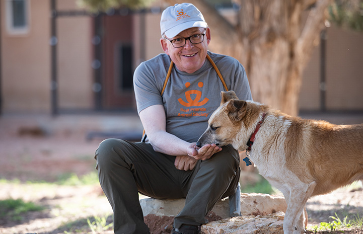 Fred, a volunteer at Best Friends Animal Sanctuary, feeding a treat to Skelly a dog in Dogtown