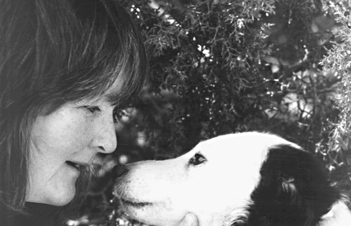 Black and white photo of Faith Maloney face-to-face with Tammy the dog