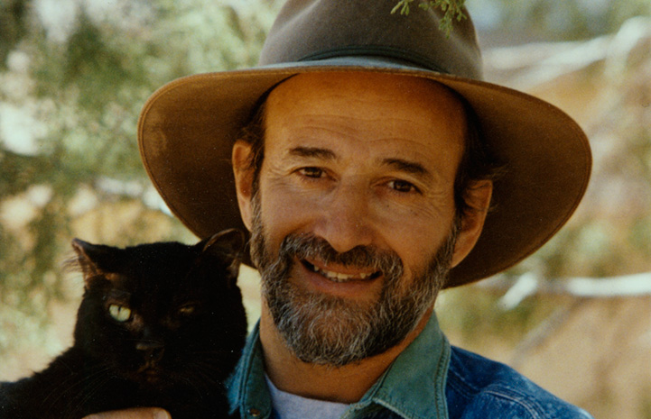 Francis Battista wearing a wide brimmed hat and holding Blackjack the cat