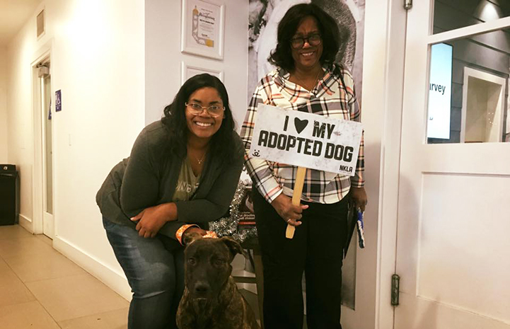 Two women next to Cuba the dog they'd just adopted, holding a sign that says I heart my adopted dog
