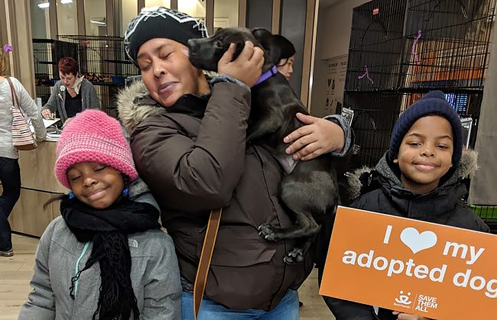 Woman carrying a black small black dog next to two children and one is holding a I heart my adopted dog sign
