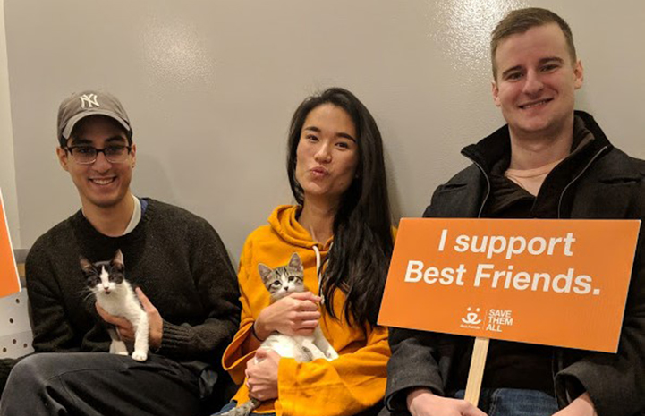 Three people holding two kittens they'd just adopted and a sign stating, I Supper Best Friends