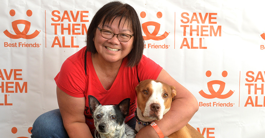 Valerie Louie with two dogs in front of a Best Friends Save Them All backdrop
