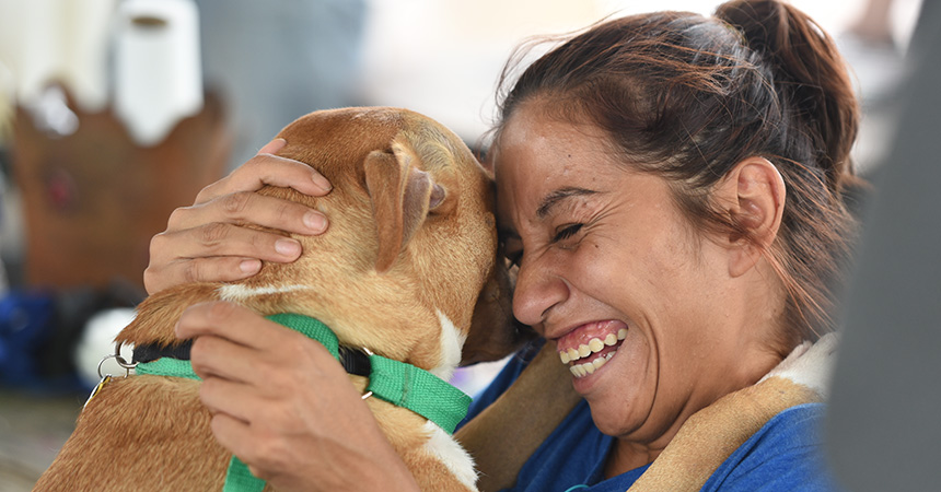 Smiling woman hugging a brown dog