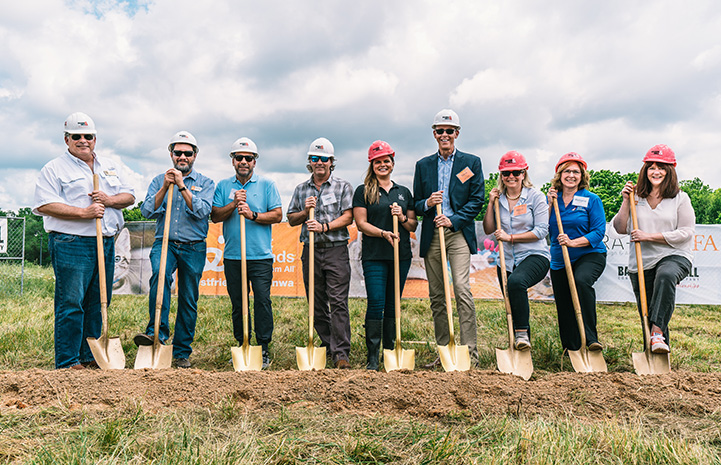 Group of people wearing hard hats and holding shovels at site for Best Friends Pet Resource Center in Northwest Arkansas