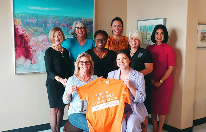 "Group of women standing in front of some paintings holding an orange T-shirt that says, ""Pets, people, community, take a stand."""