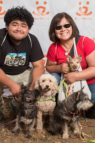 Valerie Louie and another person posing in front of a Best Friends backdrop with four small dogs