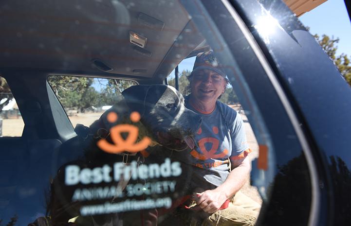 Dogtown caregiver Tom putting Jango the dog into a car with a Best Friends decal