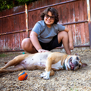 Large dog lying on the ground in front of a smiling woman