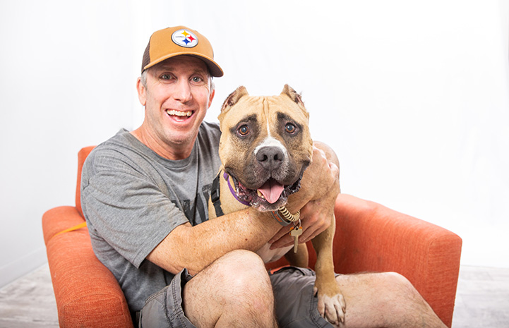 Portrait of volunteer Danny Bress with Beefy the dog sitting together on an orange chair